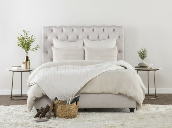 off white tufted bed in bedroom setting