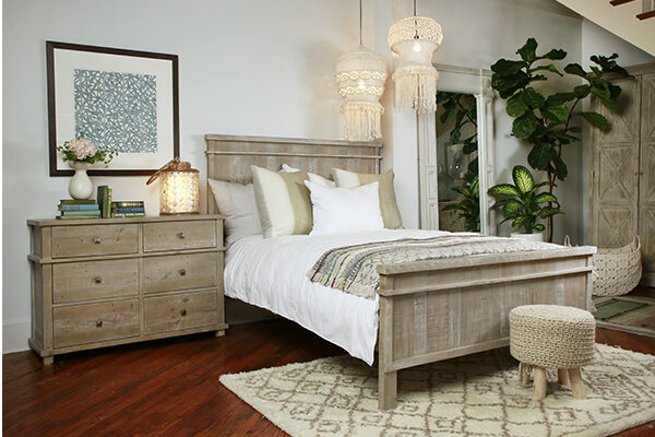 Reclaimed pine wood bed with tall headboard and distressed light brown finish seen in bedroom setting