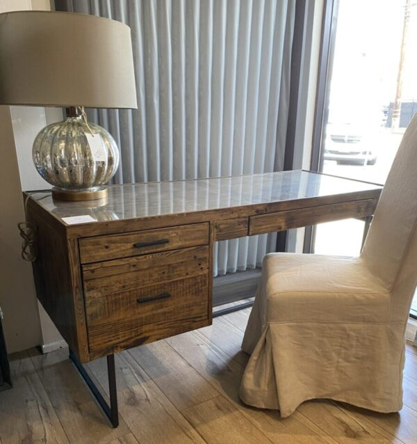Wood desk with drawers and iron frame shown with chair and lamp