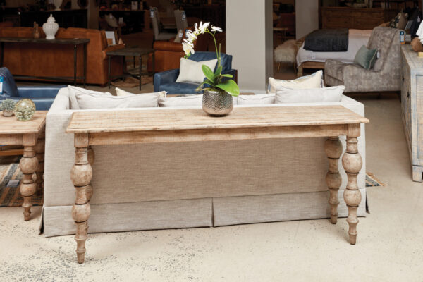 Cream color console table shown behind light cream loveseat