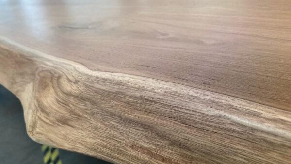 natural wood tone live edge dining table edge close up