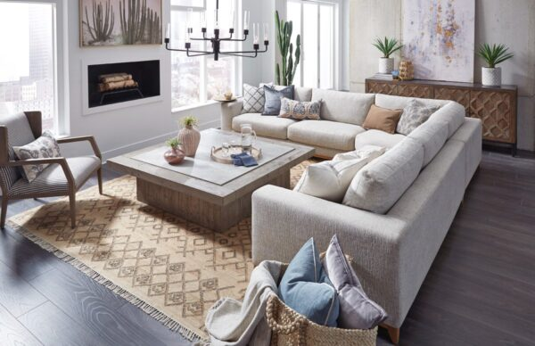 Large square wood coffee table with concrete laminate top seen in a living room with gray sectional sofa