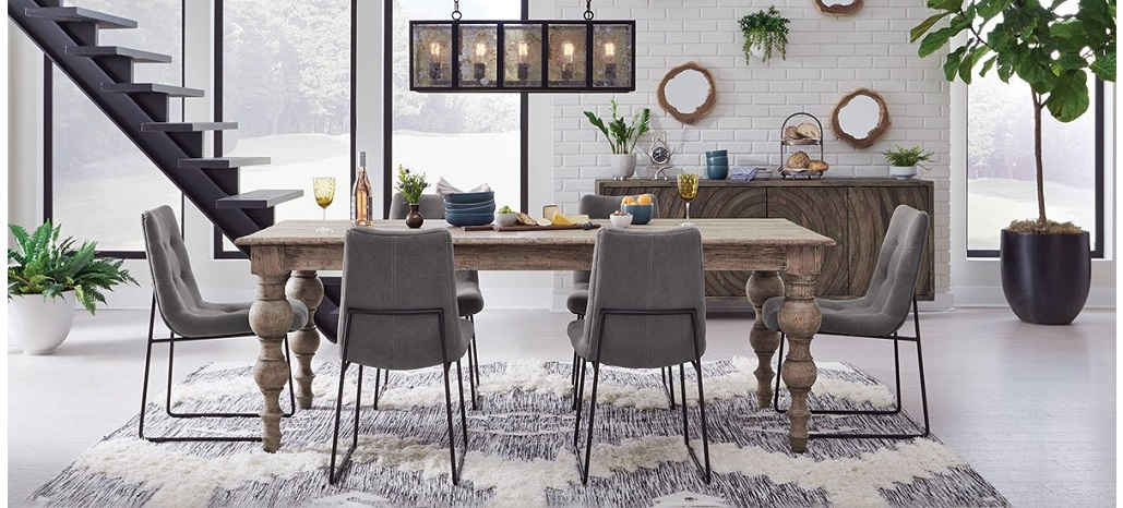 dining room setting with dining table with turned legs grey fabric dining chairs and rustic sideboard cabinet