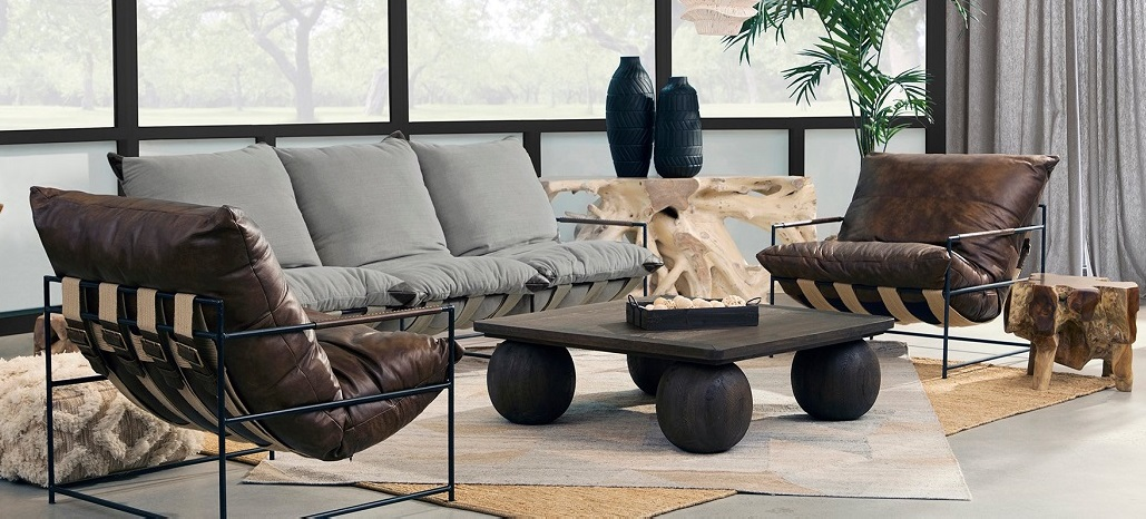 living room with dark coffee table leather club chairs grey sofa and root side table